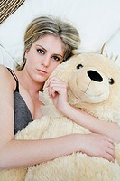 Attractive young woman with a big teddy bear
