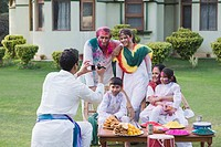 Man filming his family with a video camera on Holi