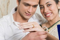 Man putting bangles on a woman´s hand