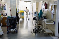 Young nurse walking a busy hospital hallway with instrumental and machines