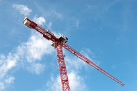 Tower crane against blue sky with a few clouds
