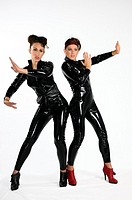 Two young women in secret agent karate mode in black plastic catsuits on white background