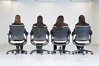 Rear view of business women sitting on office chairs
