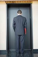Rear view of a businessman waiting for the elevator in an office building