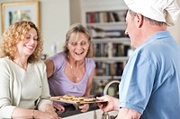 Chef serving cookies to mature women at home