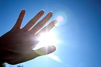 close_up of hand in front of blue sky with burning sun