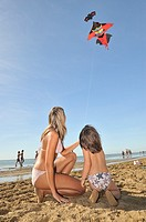 Women and children are flying kite on the beach