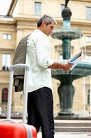 man in city street looking at map