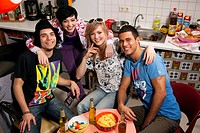 group of four friends sitting in kitchen together