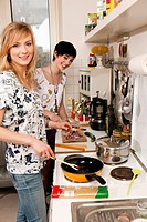 portrait of two young women cooking in kitchen