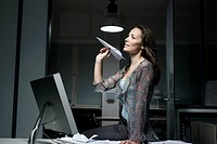 young woman in office late at night playing with paper plane