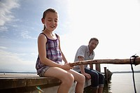 father and daughter on pier angling together