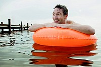 portrait of man swimming with floating tyre
