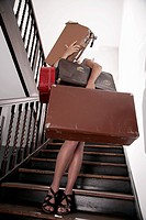 young woman in staircase trying to carry four suitcases