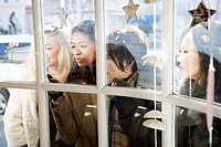 Female friends looking through window