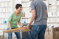 Couple carrying coffee table