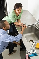 Couple doing plumbing in kitchen
