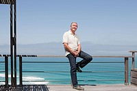 Man sitting on railing by the sea
