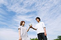Couple Standing in Park Holding Globe