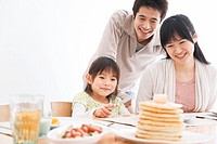 Father, mother and daughter sitting at breakfast table together