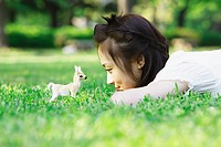 Girl Lying on Grass and Playing with Toy