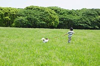 Boy Running in Park with his Pet