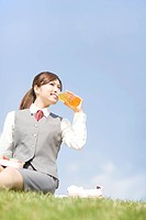 Businesswoman sitting outside drinking juice