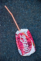 A crushed Coca Cola can with straw