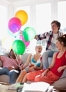 Friends with balloons sitting on sofa in living room (thumbnail)