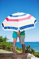 Couple under beach umbrella on patio overlooking ocean