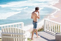 Man with bare chest talking on cell phone on patio overlooking ocean