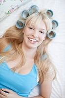 Woman laying with curlers in hair