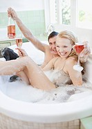 Couple in clothing drinking champagne in bathtub