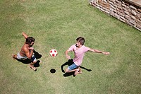 Men playing soccer on grass