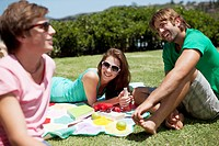Friends relaxing with books and drinks on blanket in sunny grass
