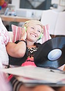 Woman laying on sofa listening to headphones and holding music record