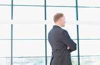 Businessman standing and looking pensively out window