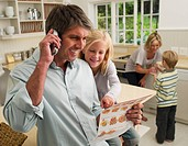 Family ordering take out food by telephone in domestic kitchen