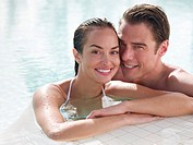 Couple in swimming pool leaning on edge