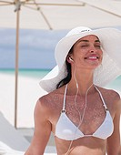 Woman in bikini wearing sun hat and listening to headphones on beach