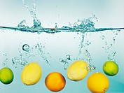 Lemons, limes and oranges splashing in water