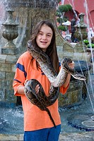 A long haired boy poses for s photo holding a python in Malacca Malaysia
