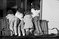 Little girls standing on a public bench