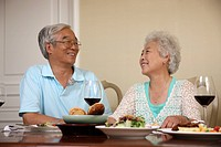 Mature couple taling at dinner table