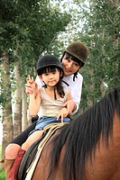 Portrait of girl riding horse with her mother