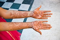 A new bride holds out her hands that are decorated in henna tattoos