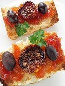 Toast with tomato confit, dried tomato and black olives