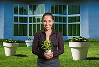 Mixed race woman holding flowers in pot (thumbnail)