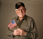 An proud American senior World War II veteran holding flag