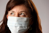 Woman wearing surgical mask to protect herself from contracting contagious influenza viruses like H1N1 Swine Flu